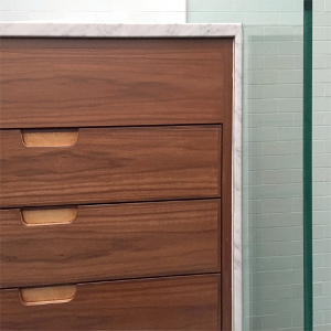New Walnut and Carrara marble vanity beside glass shower panel