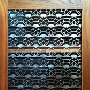 Custom laser-cut metal screen in a Walnut cabinet